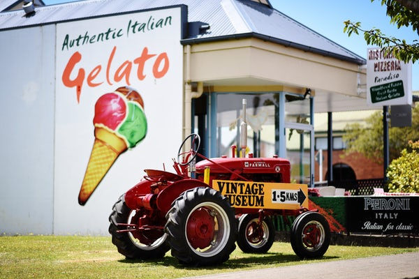 red tractor in front of storefront with gelato banner sign